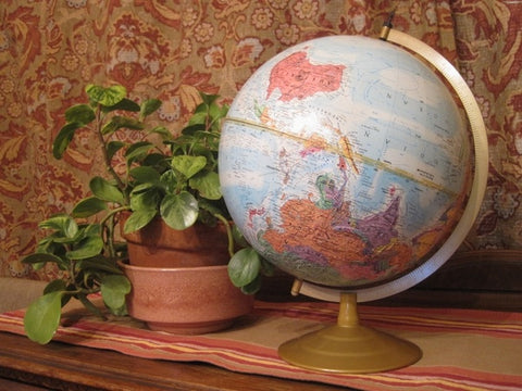 A globe that is upside down by western standards sits on a tablecloth with a plant.