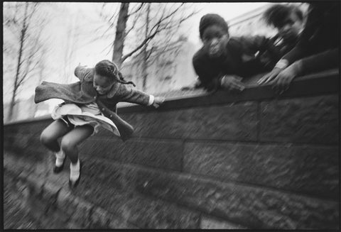 Jumping Over the Wall by Mary Ellen Mark. A young girl jumps over a stone wall while adults look on