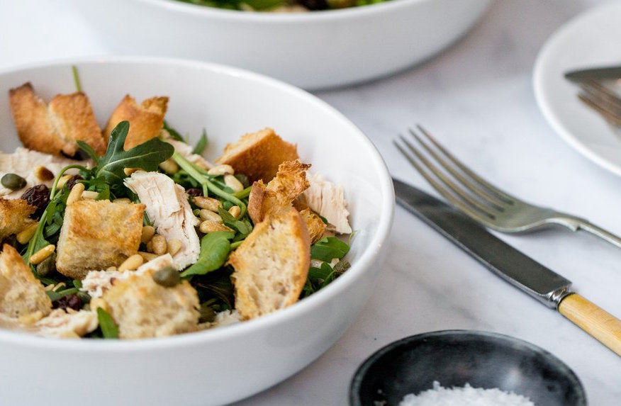Chicken and toasted bread salad with raisins, pine nuts and capers