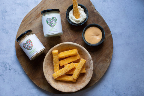 Large wooden board in the centre of the photo; this is topped with a smaller wooden bowl of crisp thick cut golden polenta chips. Above the wooden bowl is a smaller bowl of red chilli mayonnaise, with 2 jars of Lucy's vegan mayonnaise beside.