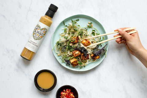 Plate of noodles with tofu on top greens, chilli and chopsticks tucking in. On the left, there is a bottle of Lucy's ginger and sesame, with 2 smaller bowls next to it of dressing and chopped up chilli.