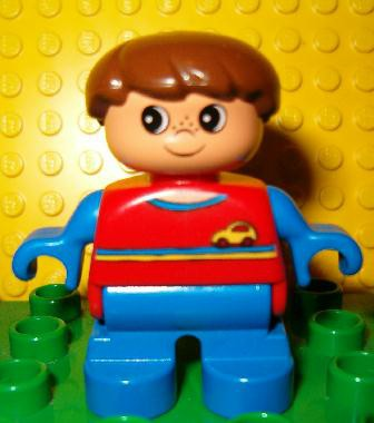 Duplo Figure, Child Type 2 Boy, Blue Legs, Red Top with Yellow and Blue Stripes and Yellow Car Logo, Blue Arms, Brown Hair