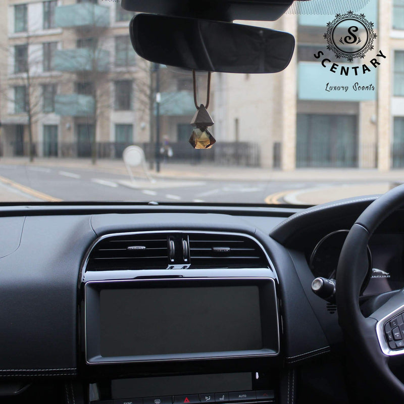 Glass scent diffuser hanging from rearview mirror with a view of a car dashboard