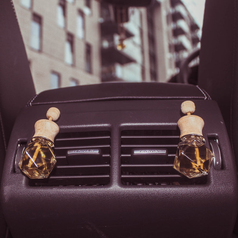 Closeup image of a pair of glass scent diffusers hanging from rear passenger A/C ducts