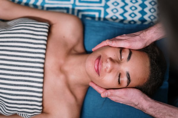 Relaxed woman receiving facial massage