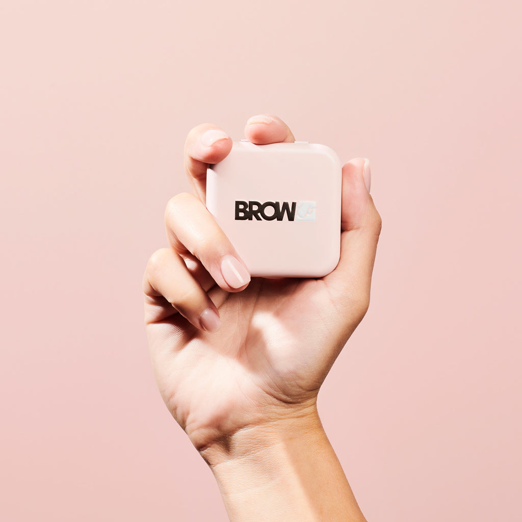 Female hand holding a BROWKO tin on a pink background