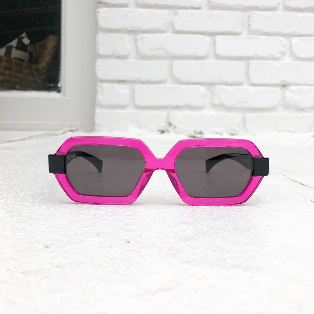 A pair of neon pink and black sunglasses by Gem+Elli on a white floor