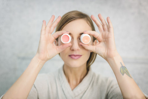 Woman holding moisturizers to eyes