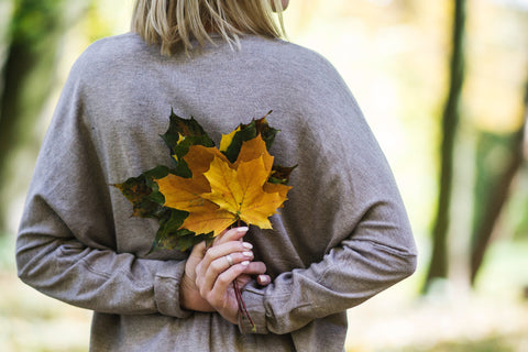 Woman holding leaves behind her back