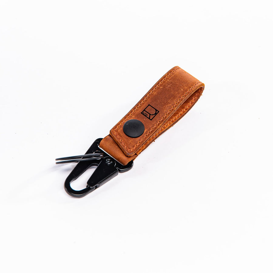 Angled view of the tan leather Ignition Clip Key Carry showcasing the clip, the key ring, and the snap attachment.