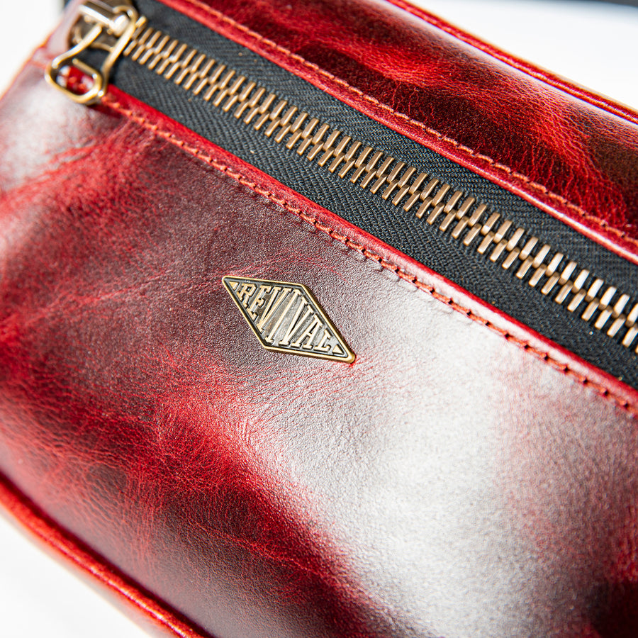 Close up detail shot of the brass Revival logo and zipper on the oxblood Kilo Bag