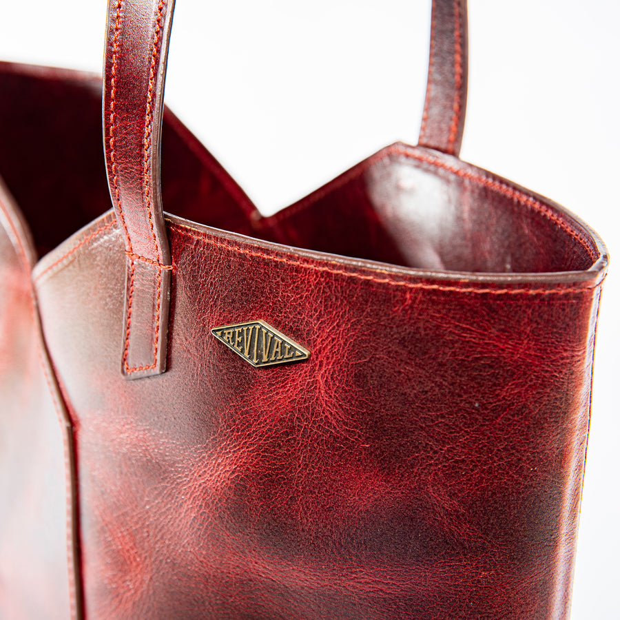 Close up detail shot of the brass Revival emblem on the oxblood Terlingua Tote
