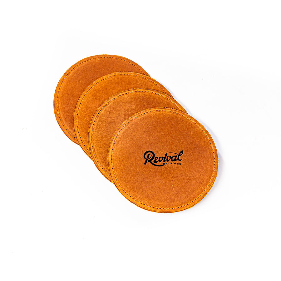 A set of 4 tan leather coasters with suede bottoms and featuring a Revival Limited stamped.