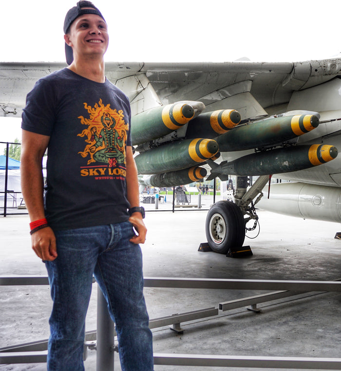 Man wearing the WETSU Airborne Sklords Collab with Wrm.fzy Shirt next to a jet