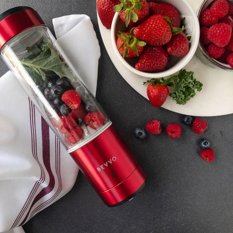 Red BEVVO Portable Blender with raspberries, blueberries, kale and strawberries inside.