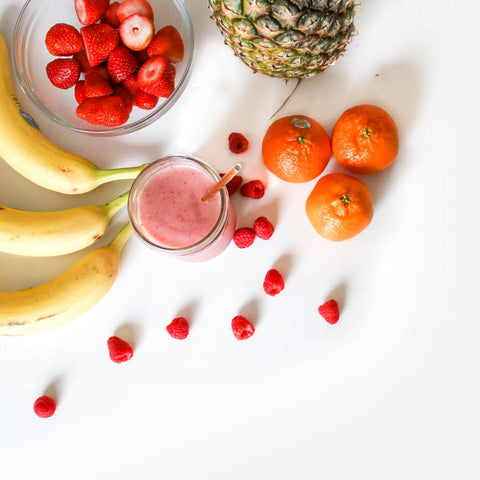 Overhead picture of three bananas, a bowl strawberries, a pineapple, raspberries, tangerines and a pink smoothie in a glass with a straw in it.