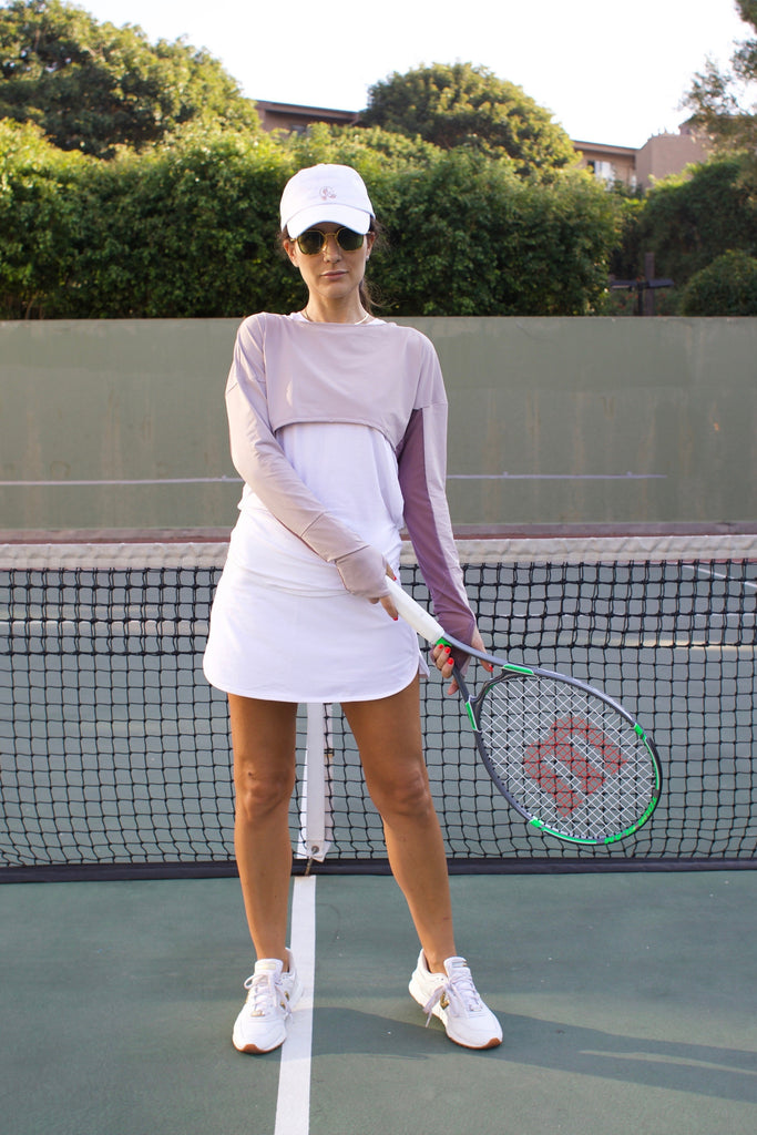 Woman playing tennis wearing lightweight UPF 50+ (sun-protective) crop top with hand protection in iris.