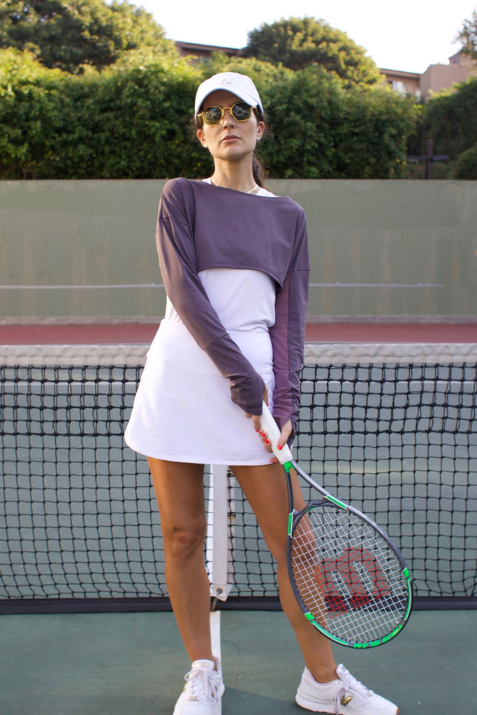 Woman playing tennis wearing lightweight UPF 50+ (sun-protective) crop top with hand protection in plum.