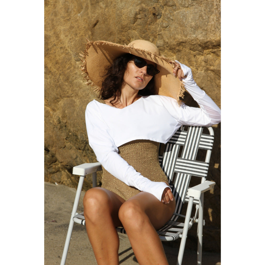 Woman at the beach wearing white lightweight UPF 50+ (sun-protective) crop top with hand protection.
