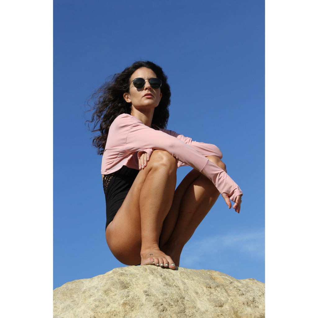 Woman at the beach wearing pink lightweight UPF 50+ (sun-protective) crop top with hand protection.