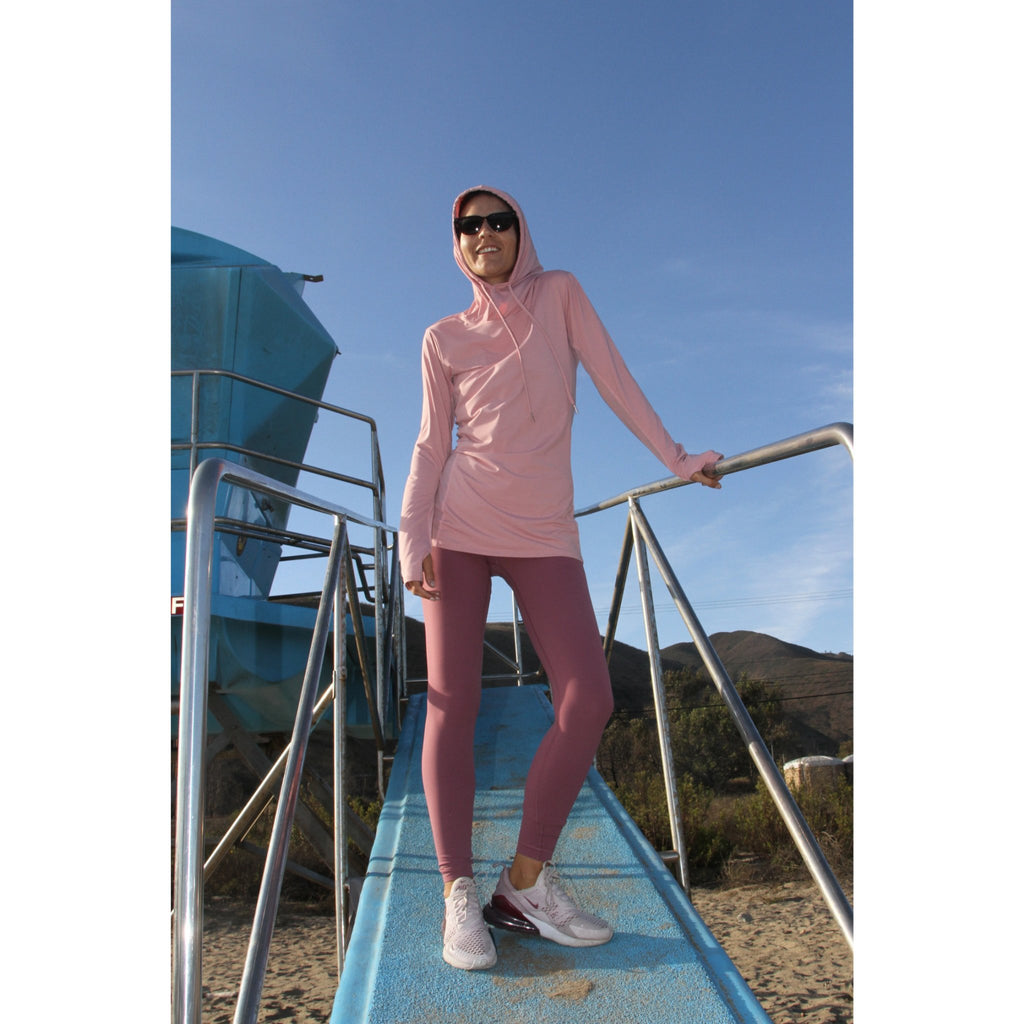 Woman on a beach wearing a long-sleeved UPF 50+ (sun protective) shirt with full hood and hand protection in pink/blush.