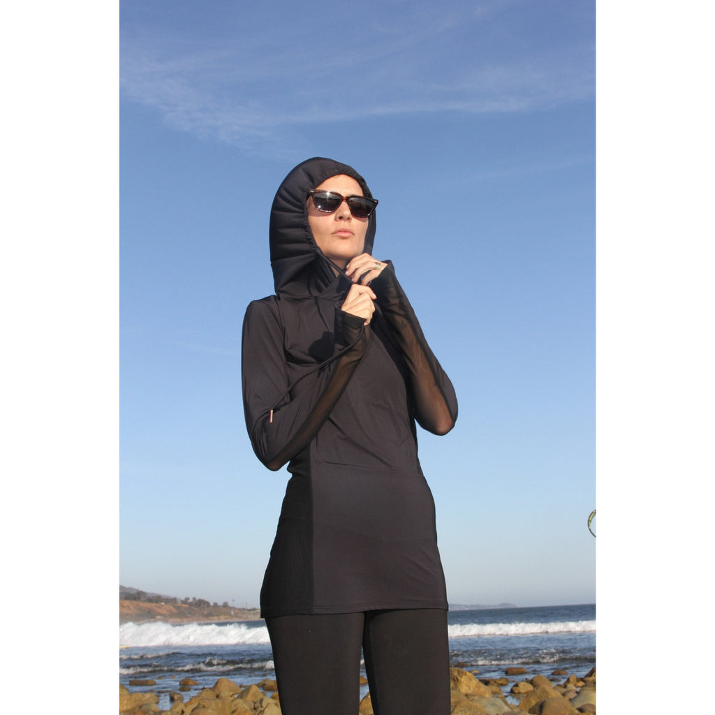 Woman on a beach wearing a long-sleeved UPF 50+ (sun protective) shirt with full hood and hand protection in black.