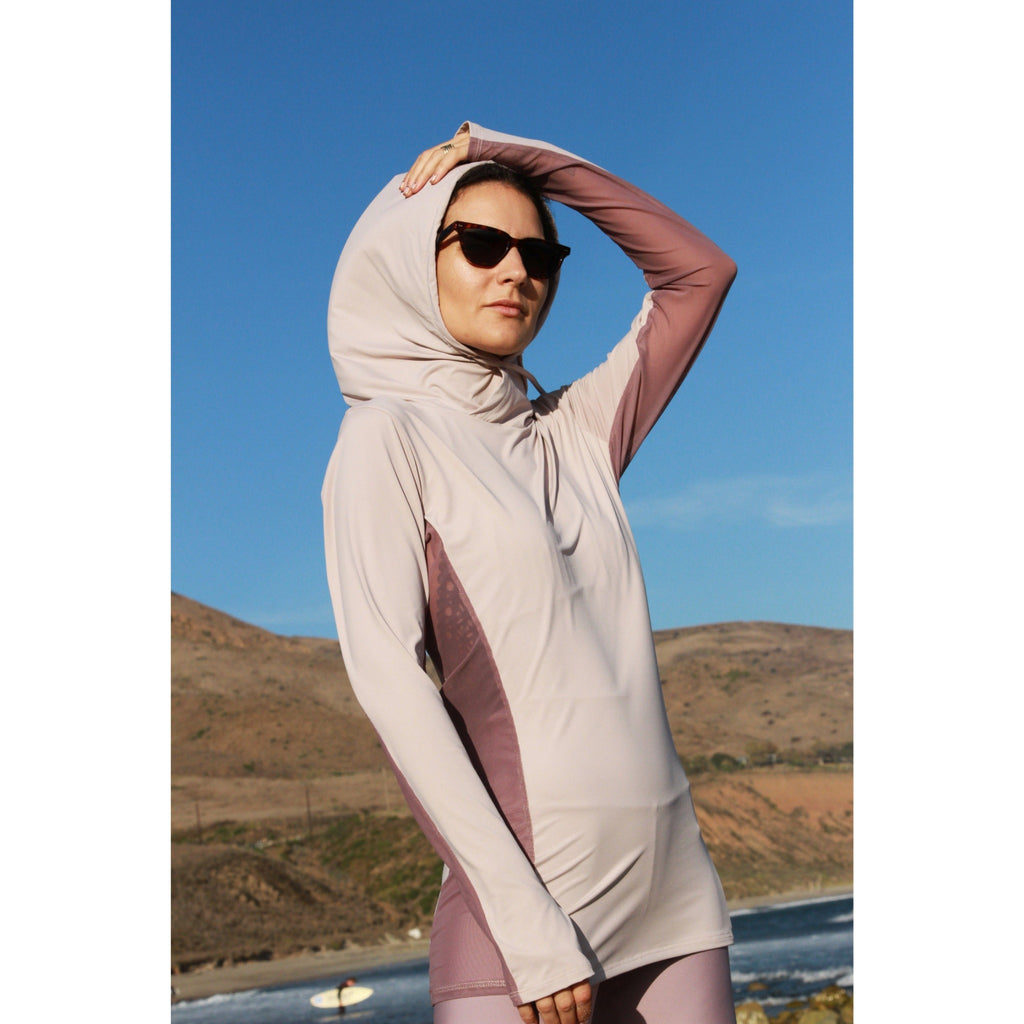 Woman on a beach wearing a long-sleeved sun protective shirt with full hood and hand protection in iris.