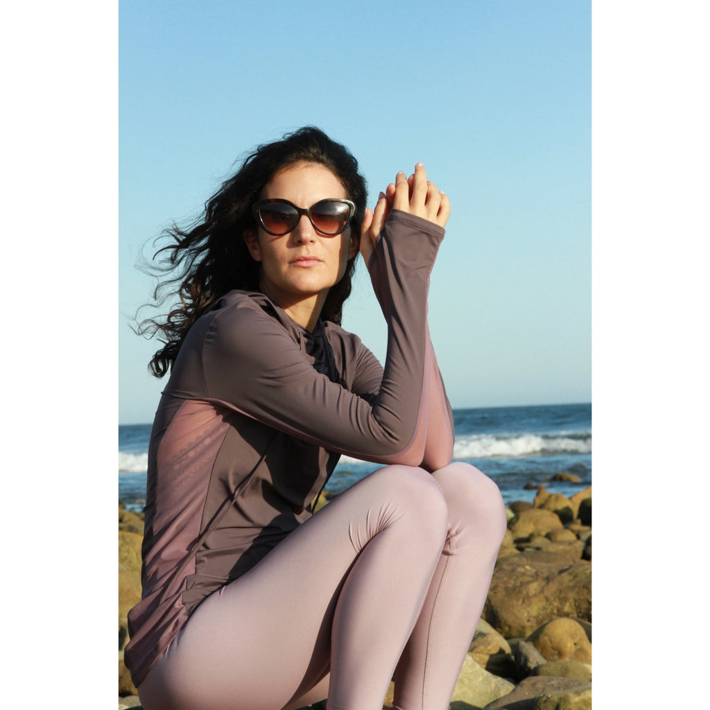 Woman on a beach wearing a long-sleeved UPF 50+ (sun protective) shirt with full hood and hand protection in plum.