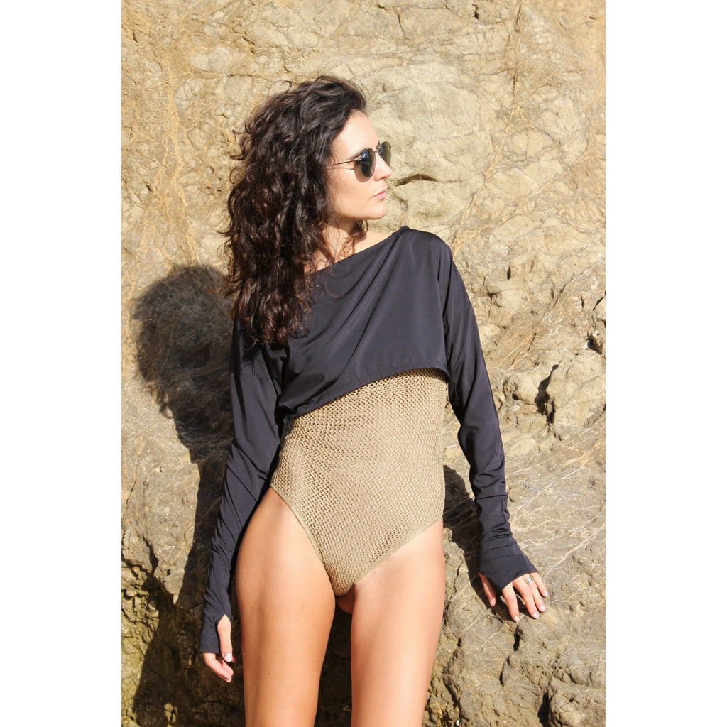 Woman at the beach wearing light weight UPF 50+ (sun-protective) crop top with hand protection.
