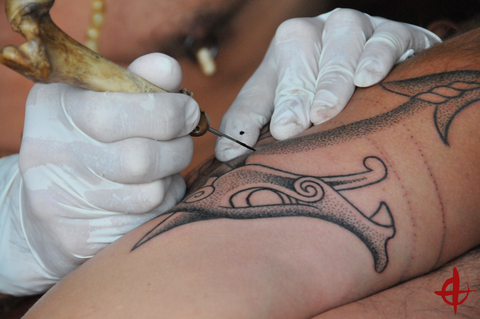 Colin Dale shown hand poking a dragon design into the skin of a client with a bone handled tattoo needle