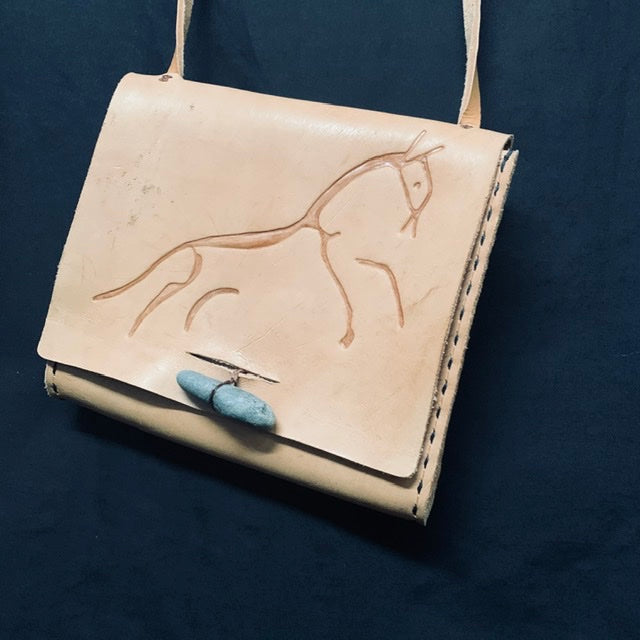 hand carved leather handbag, ancient rock art, uffington horse, celtic art by sacred knot