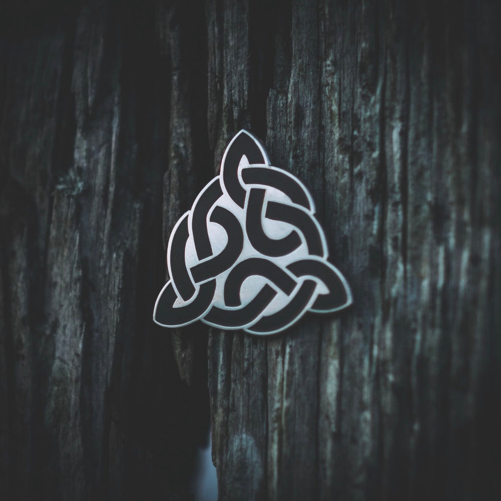 Enamel pin by Sean Parry showing the Sacred Knot Tattoo logo