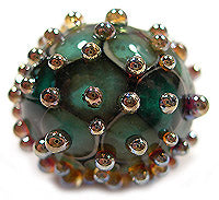 Example of Iris Gold Frit dots on a bead by Glass Diversions