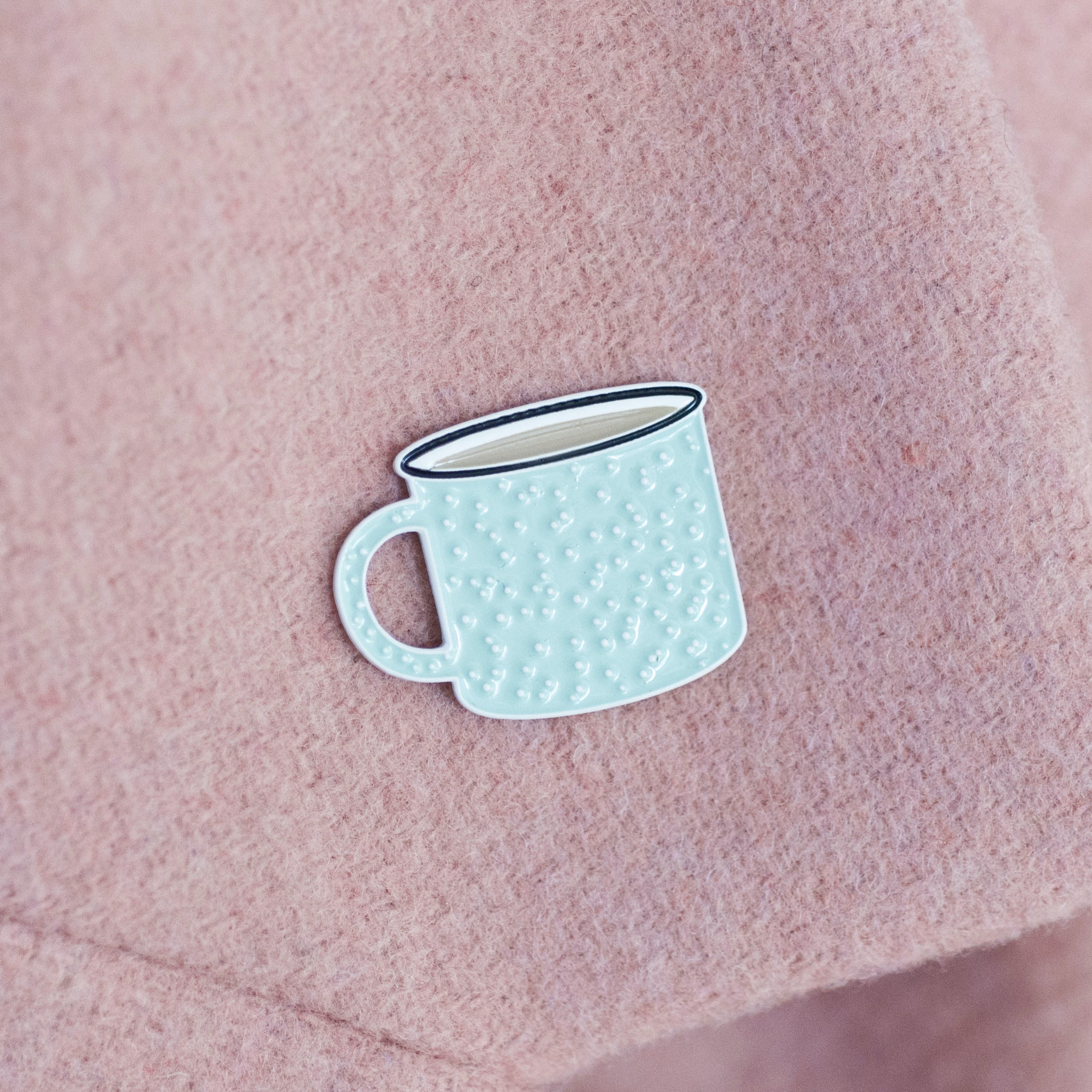 Mint coloured enamel pin in the shape of a camp style coffee mug.