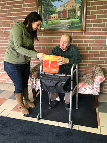 Founder Ali Izzo smiling while delivering Purpose Box to Senior man with front wheeled walker | Purpose Sponsor a Senior Program