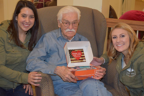 Founders Ali Izzo ( Left) and Holly Masters (Right) delivering a Purpose Box to an older male smiling | Purpose Sponsor a Senior