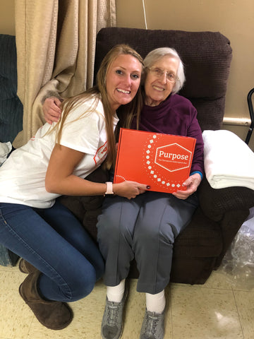 Founder Holly Masters delivering a Purpose Box to a senior women with a bright smile | Purpose Sponsor a Senior Program