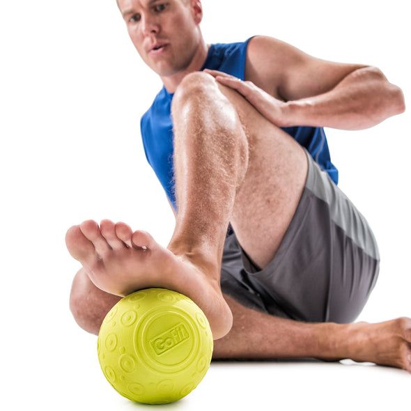 Male rolling bottom of foot with Massage Ball