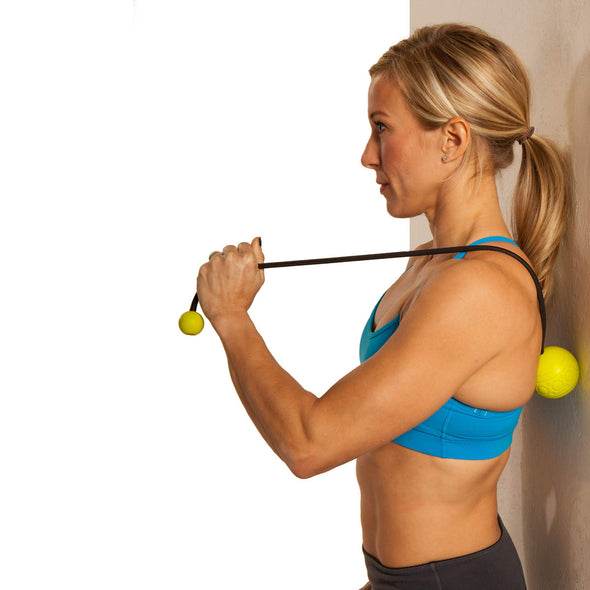 Female rolling mid back against wall w/ GoBall - Targeted Massage Ball