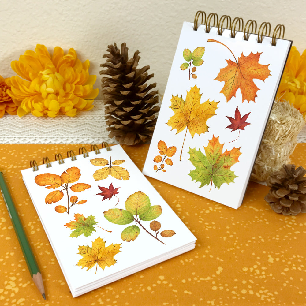 4x6 wire bound notebooks with watercolor paintings of fall leaves on the covers.