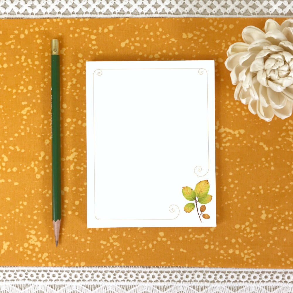 Unlined notepad with a watercolor autumn leaf in bottom right corner.