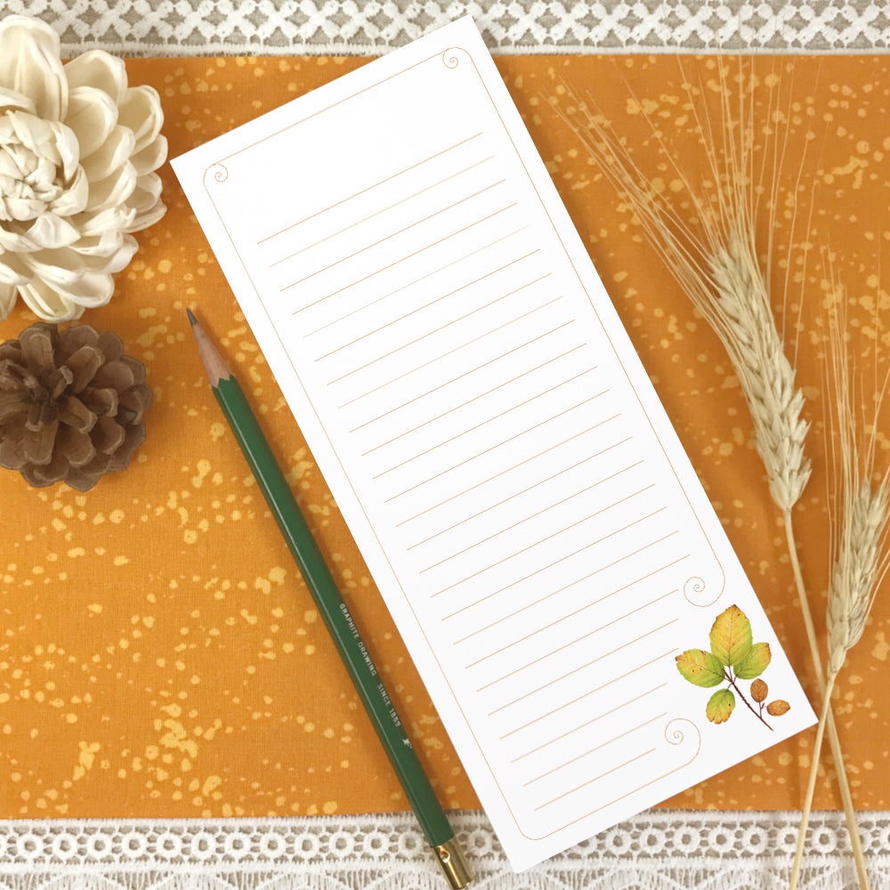 Tall lined notepad with watercolor autumn leaves in bottom right corner.