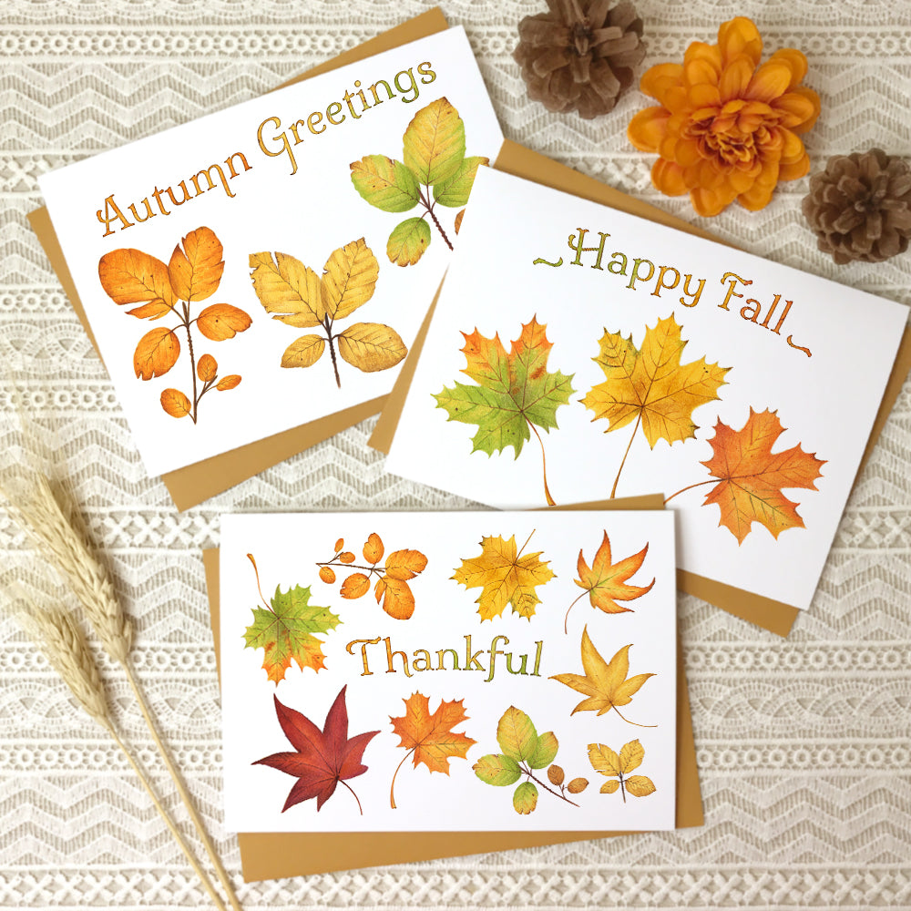 "Set of three autumn greeting cards with watercolor paintings of fall leaves titled, ""Autumn Greetings"", ""Happy Fall"", and ""Thankful""."
