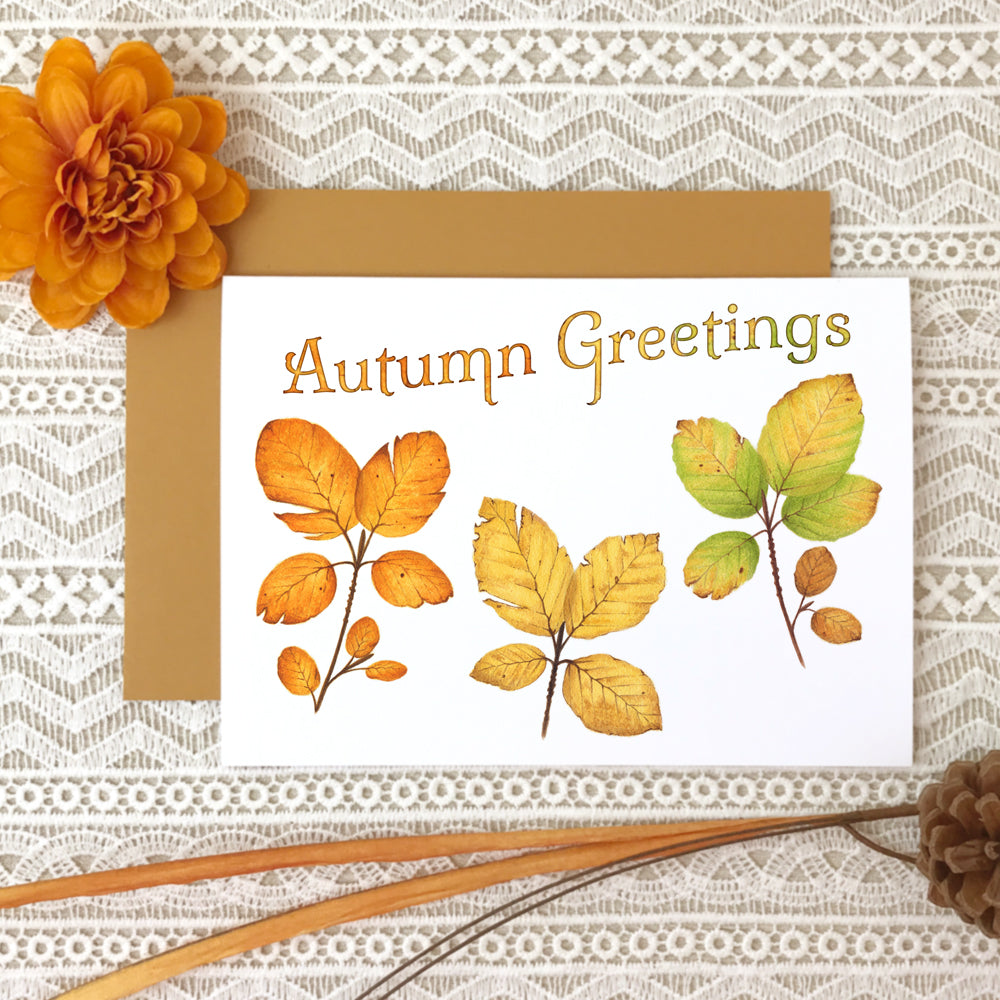 "Fall greeting card with watercolor paintings of three beech leaves in orange, gold and green and the title ""Autumn Greetings"""
