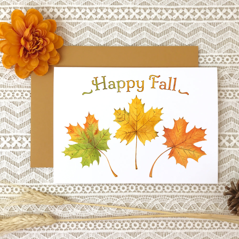 "Autumn greeting card titled ""Happy Fall"" with watercolor paintings of three maple leaves in green, yellow and orange."