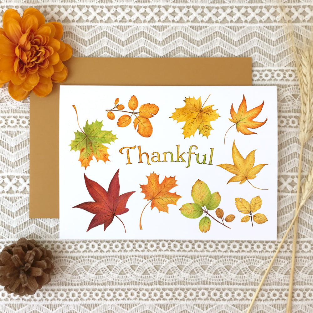 "Thanksgiving greeting card with a collage of watercolor painted fall leaves surrounding the title, ""Thankful""."