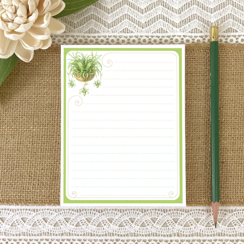 Small lined notepad with illustration of a cute spider plant in upper left corner.