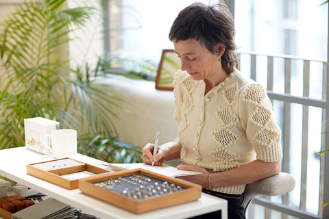 Ruth Tomlinson sitting at a jewelry design table.