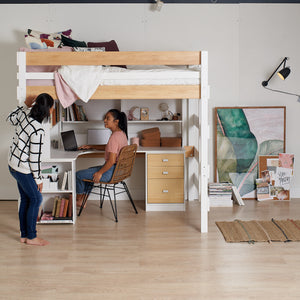 Double loft bed sits above L shaped desk study with storage