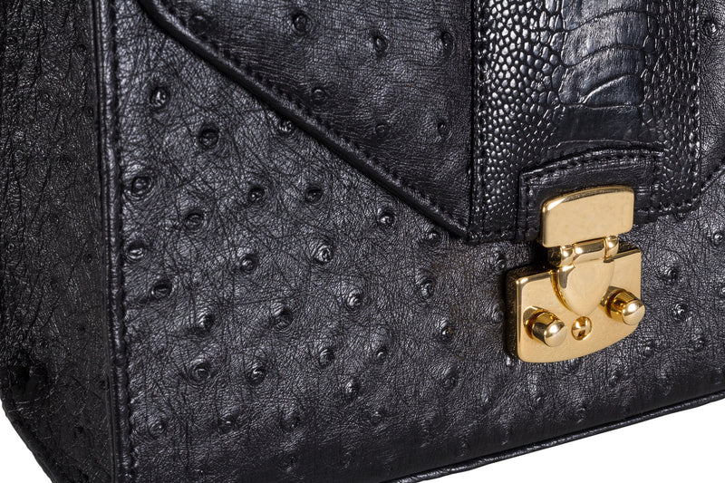 Detailed view black ostrich and shin constructed top flap handbag with an Italian lock closure. Contains inside back zipper pocket and a front inside zip pocket. High quality black leather interior. Includes a top handle with 24 carat gold plated fittings, detachable shoulder strap, adjustable buckle. Bottom bag feet studs.